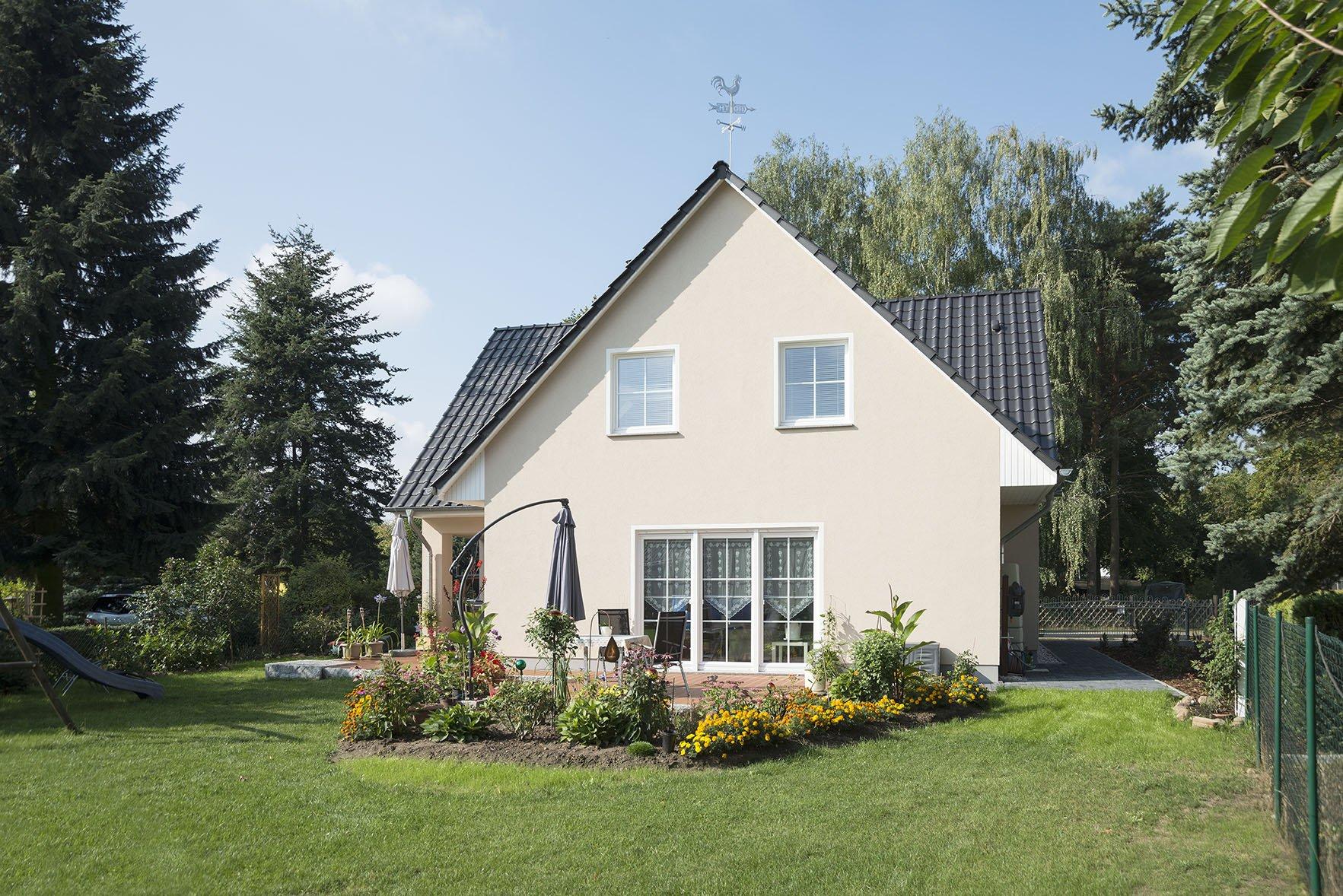 Dreigiebelhaus von Roth-Massivhaus mit Einliegerwohnung von der Gartenseite.