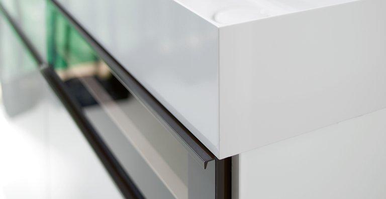 Mineralgusswaschtisch und Waschtischunterschrank sind durch ein konsequent bündiges, flächiges Design verbunden, betont noch durch das einheitliche Frontmaß von Waschtisch und Schublade.