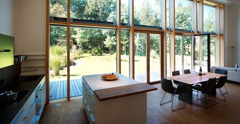 Für lichtdurchflutete Räume und fließende Übergänge von innen nach außen sorgt die Pfosten-Riegel-Fassade von Kneer-Südfenster, die sich über zwei Vollgeschosse nach Süden orientiert.