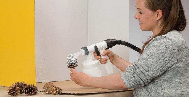 Der Studio Home Decor Sprayer von WAGNER lässt Tannenzapfen schneebedeckt aussehen.