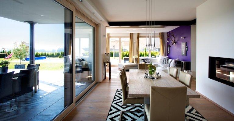 Großformatige Hebe-Schiebe-Türen sorgen für lichtdurchflutete Räume und öffnen sie mit barrierefreiem Übergang zur Terrasse.