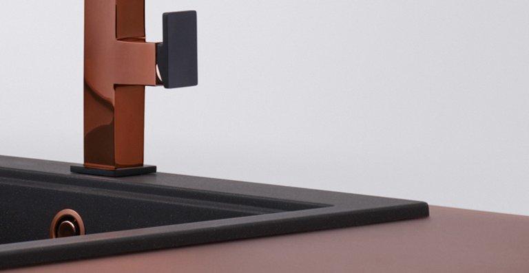 Die onyx-farbenen Spülen Mythos und Kubus aus Fragranit+ setzen die Kupferelemente in Szene. Auch die Zugauslauf-Armatur Centinox beindruckt durch in der kontrastarken Farbkombination.