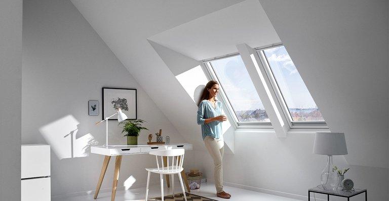 """Mehr Kopffreiheit und Ausblick bietet auch die Lichtlösung """"Raum"""". Durch den Einsatz des Aufkeilrahmens rückt die Oberkante des Fensters weiter nach außen, sodass Mieter oder Eigentümer auch bei Dächern mit einer Neigung von weniger als 35 Grad bequem vor dem Fenster stehen können."""