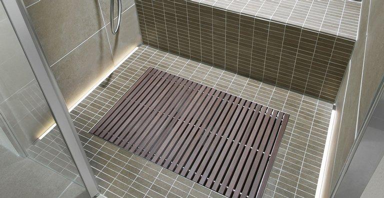 Durch das vielseitig einsetzbare LED-Leuchtprofil bietet ACO Lightline Pro individuelle Möglichkeiten zur Licht- und Bodengestaltung in Badezimmern. Hier ist es verlegt entlang der Seitenwände der Duschnische. Ebenfalls zu sehen: Entwässerungslösung ACO Walk-In.
