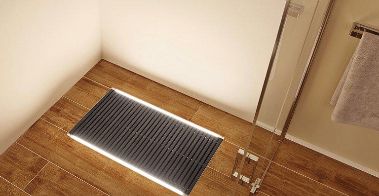 Das Bodenbeleuchtungssystem ACO Lightline Pro, leuchtend, verlegt entlang der Edelstahl-Entwässerungswanne von ACO Walk-in.