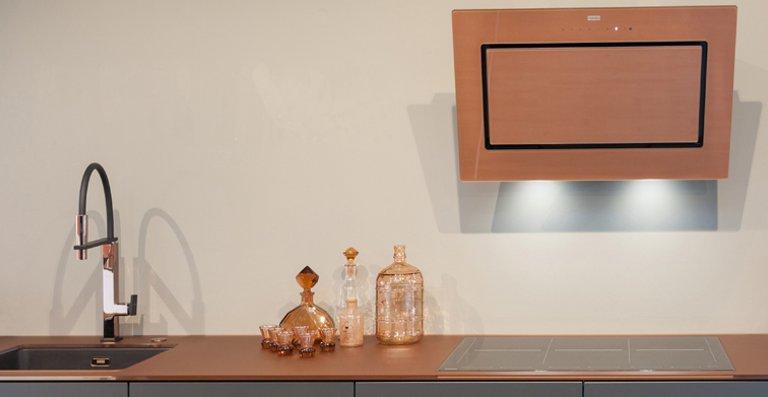 Die erfolgreiche Mythos Kopffreihaube wird mit der kupferfarben hinterdruckten Glasfront zum strahlenden Highlight der Küche. Drei Breiten bieten noch mehr Planungsflexibilität. Die LED-Spots befinden sich an der Haubenunterseite.