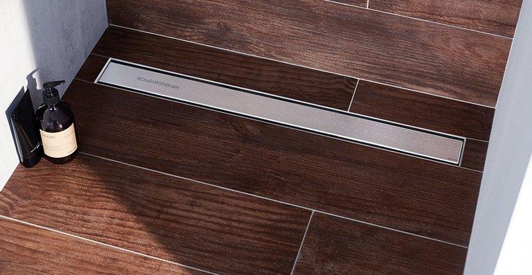 Der neue, mit Logo, Signet oder Schriftzug individualisierbare Design-Rost ACO Signature in der bodenebenen Edelstahl-Duschrinne ACO Showerdrain M, Länge 800 mm.