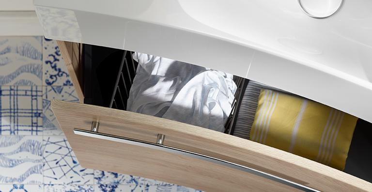 Der Waschtischunterschrank verfügt über eine innen liegende Steckdose und einen als Handtuchreling dienenden Griff.