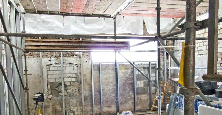Bei dem Einbau des Badezimmerkubus bilden schwere Stahlträger das Grundgerüst, die anschließend mit massiven Holzbalken verschraubt werden.