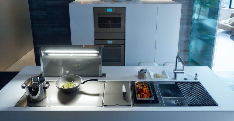 Die Dunstabzugshaube wird automatisch mit dem Kochfeld aktiviert, passgenaue Spüleneinsätze erlauben verschiedene Küchenarbeiten direkt über dem Becken.