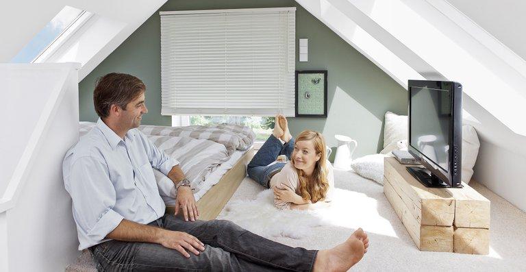 Auf dem Spitzboden angelangt erwartet das Paar ihr gemütliches und lichterfülltes Schlafzimmer. Beim Einschlafen genießen beide den Blick in den Sternenhimmel.
