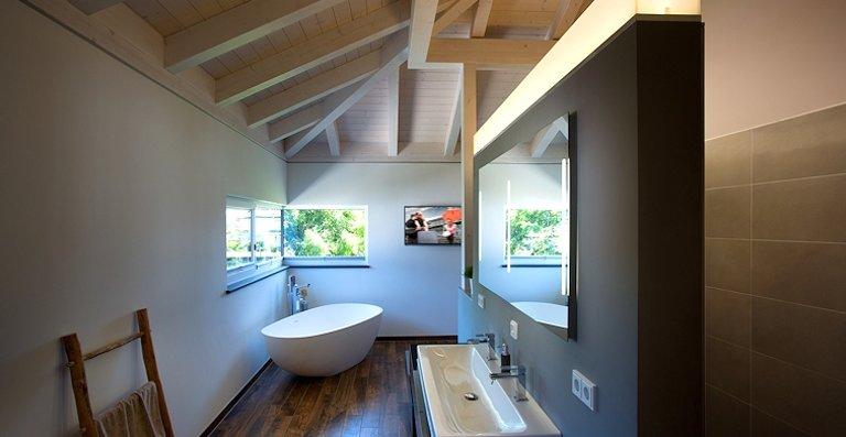 Eine Ganzglasecke sorgt im edel ausgestatteten Bad dafür, dass sich von der Badewanne aus der unverbaute Ausblick genießen lässt.