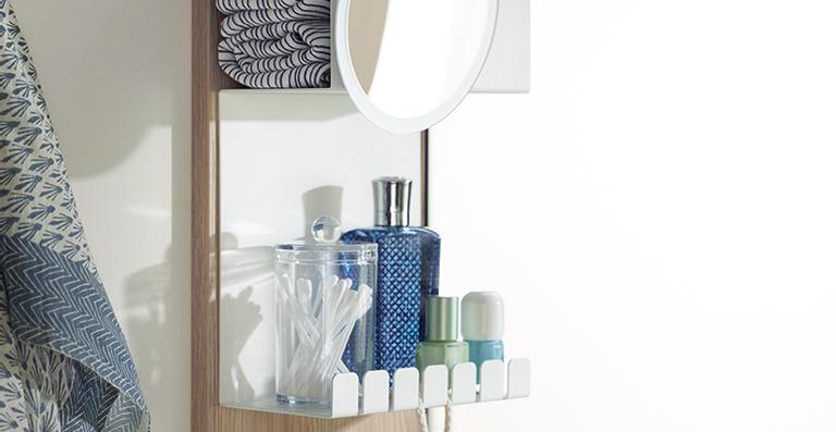 Die schmalere-rückwärtige Spiegelfläche lässt Platz für eine metallene Wandablage samt Vergrößerungsspiegel.
