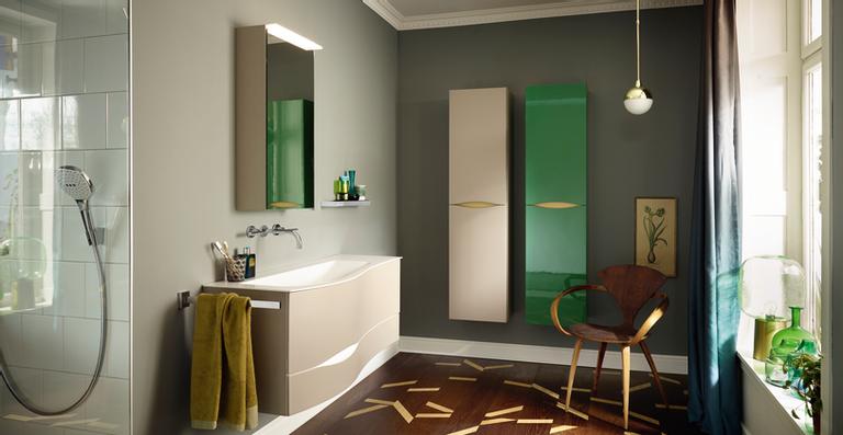 Die weich geschwungene Formensprache des neuen Sinea 2.0 Programms von burgbad mit seinen organischen Details wie etwa der farblich absetzbaren Griffmulde lädt ein zur exklusiven Farbgestaltung individueller Interieurs – hier in einer Lack-Kombination von Basaltgrau, Weiß, Gold und einer nach Kundenwunsch in RAL gefertigten, grünen Schrankfront.