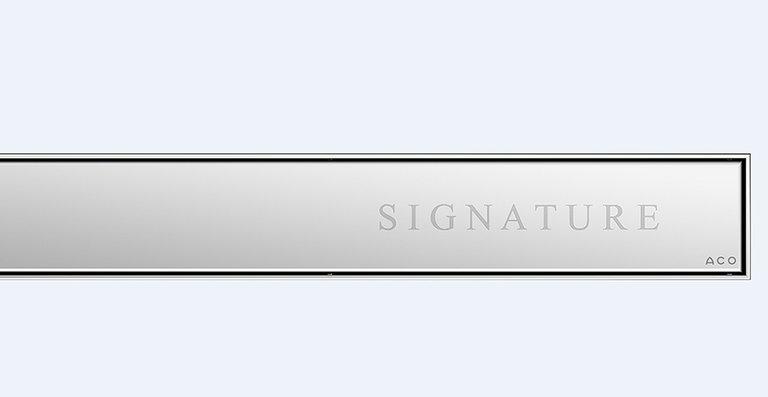 Der neue, mit Logo, Signet oder Schriftzug individualisierbare Design-Rost ACO Signature für die bodenebenen Edelstahl-Duschrinnen ACO Showerdrain E+, E, M und ACO ShowerFloor für Linienentwässerung.