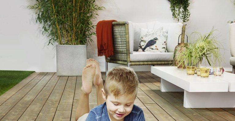 Unbeschwertes Sommerglück: Auf nachhaltig produzierten und schadstofffreien Terrassendielen kann der Nachwuchs sorglos spielen, während die Eltern entspannt das Leben draußen genießen.
