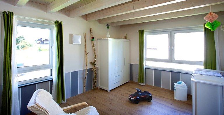 Im Dachgeschoss betonen Holzböden und Deckenuntersichten die Liebe der Bauherren zu diesem Naturbaustoff, die Fenster setzen die Räume in Szene.