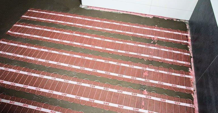 Die 30 cm breiten AEG Heizmatten werden in Bahnen verlegt. Dabei dürfen die Heizleiter nicht durchtrennt werden. Ein Bodentemperaturfühler ergänzt das System und kommuniziert mit dem Fußbodentemperaturregler.