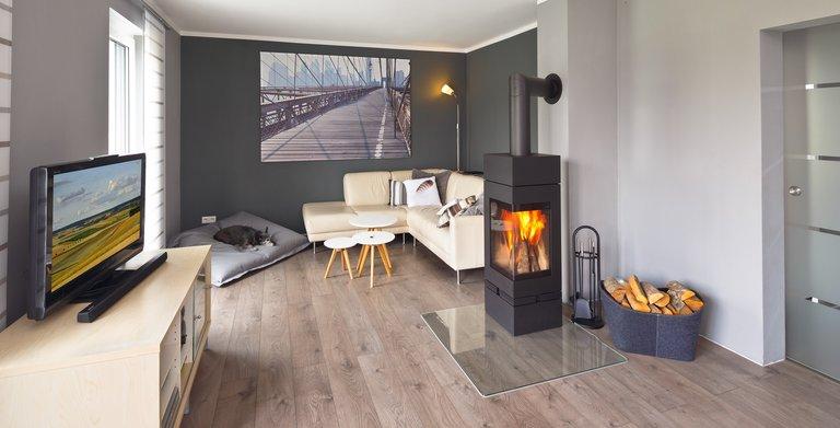 In der Sofaecke mit Kamin können die Bauherren es sich gemütlich machen. Copyright: Heinz von Heiden GmbH Massivhäuser