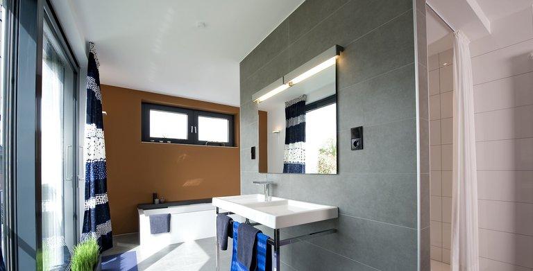 Das Elternbad ist direkt mit dem Schlafzimmer verbunden, neben einer bodengleichen Dusche gibt es auch eine Badewanne sowie einen Doppelwaschtisch.  Copyright: Heinz von Heiden GmbH Massivhäuser