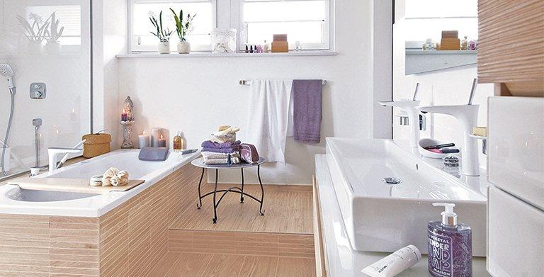 Im Masterbad verbindet ein Podest die Badewanne mit dem Waschtisch. Möbelfronten und Fliesen in Holzoptik verschmelzen zu einem harmonischen Gesamtbild. Copyright: