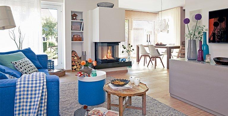 Behagliche Wärme spendet der lodernde Kamin, der - vom Sofa und vom Esstisch gut einsehbar - mitten im Raum liegt. Copyright: