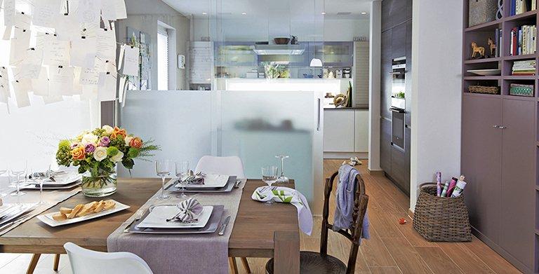 Am großen Esstisch im Erker kommt die Familie zum Abendessen zusammen. Eine satinierte Glaswand mit Schiebetüren trennt den Raum von der Küche ab. Copyright: