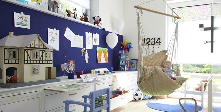 Hinter der Schiebetür im Wohnbereich liegt das Paradies. Hier können die Kleinen toben und malen. Die Kunstwerke hängen magnetisch an der Wand. Copyright: