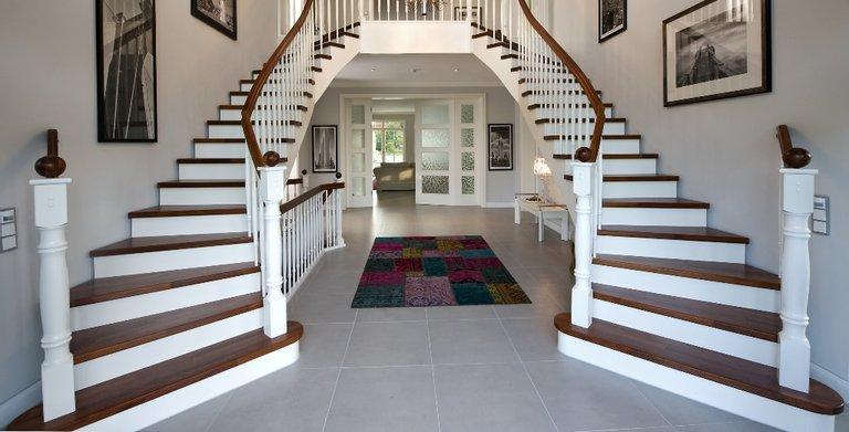 Der Eingangsbereich ist besonders repräsentativ gestaltet. Hier empfangen eine weitläufige Galerie und eine imposante Treppe mit zwei Aufgängen die Musterhaus-Besucher. Copyright: Heinz von Heiden GmbH Massivhäuser