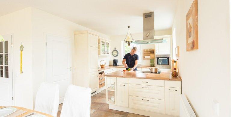 Die helle Küche im Landhausdesign mit Essbereich ist direkt mit dem Wohnbereich verbunden.  Copyright: Heinz von Heiden GmbH Massivhäuser