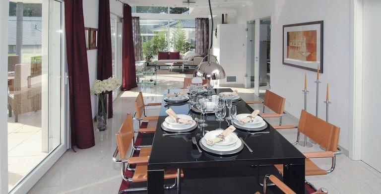 Verglaste Schiebetüren öffnen das Wohnzimmer zur überdachten Terrasse Copyright: WeberHaus