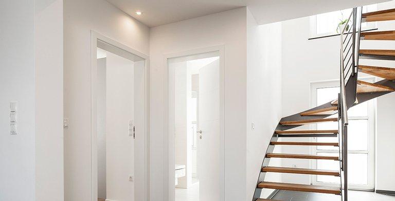 Der Treppenaufgang ins Obergeschoss erfolgt über eine elegant gewendelte Treppe Copyright: Wolf-Haus