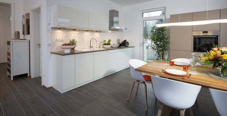 Die offene Küche mit dem angegliederten Essbereich bietet Platz zum gemeinsamen Kochen, Essen und Beisammensein. Copyright: Heinz von Heiden GmbH Massivhäuser